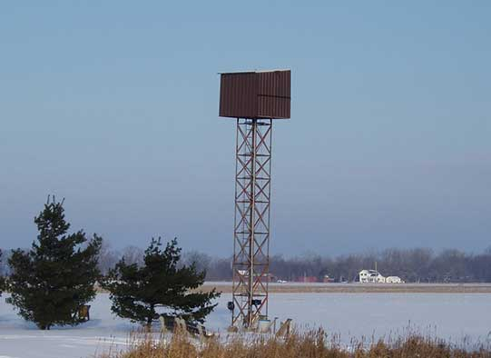 Lookout tower in the middle of a snowy field.