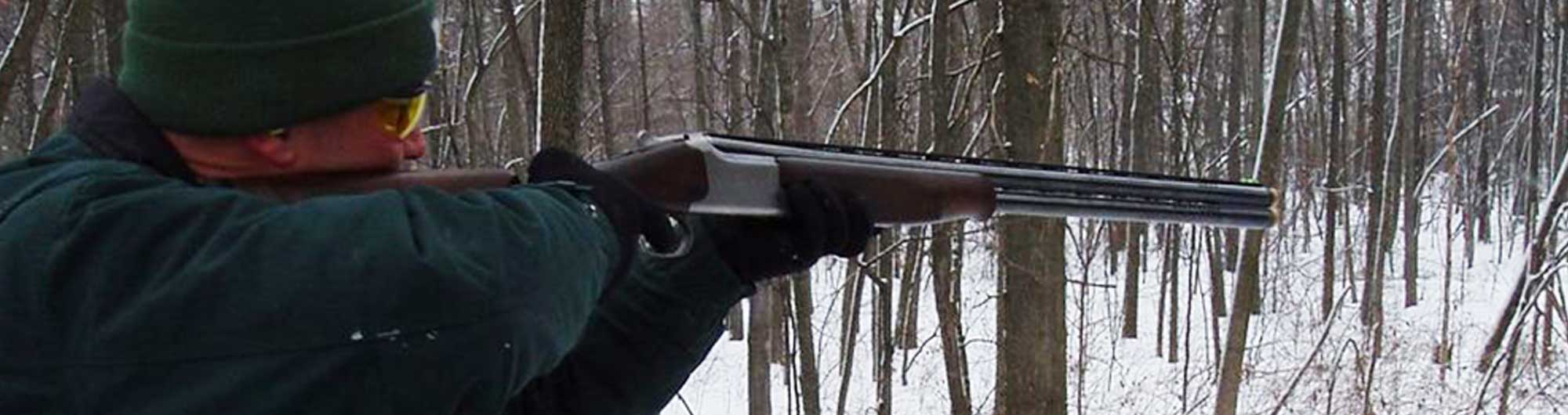 Hunter aiming his gun in a snowy woodland scene.